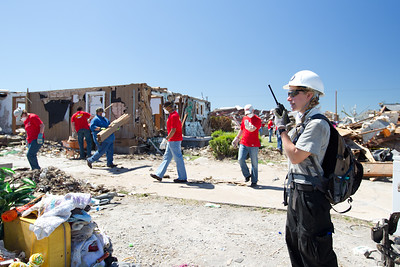 An AmeriCorps NCCC member directs Kansas City Chief players at a volunteer site in Joplin, MO. (Photo by Scott Julian, 2011).