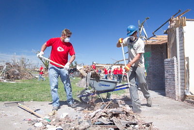 Mark Wilson, part of the Iowa Conservation Corps, works with a Kansas City Chiefs player to clean up debris in Joplin, MO. (Photo by Scott Julian, 2011)