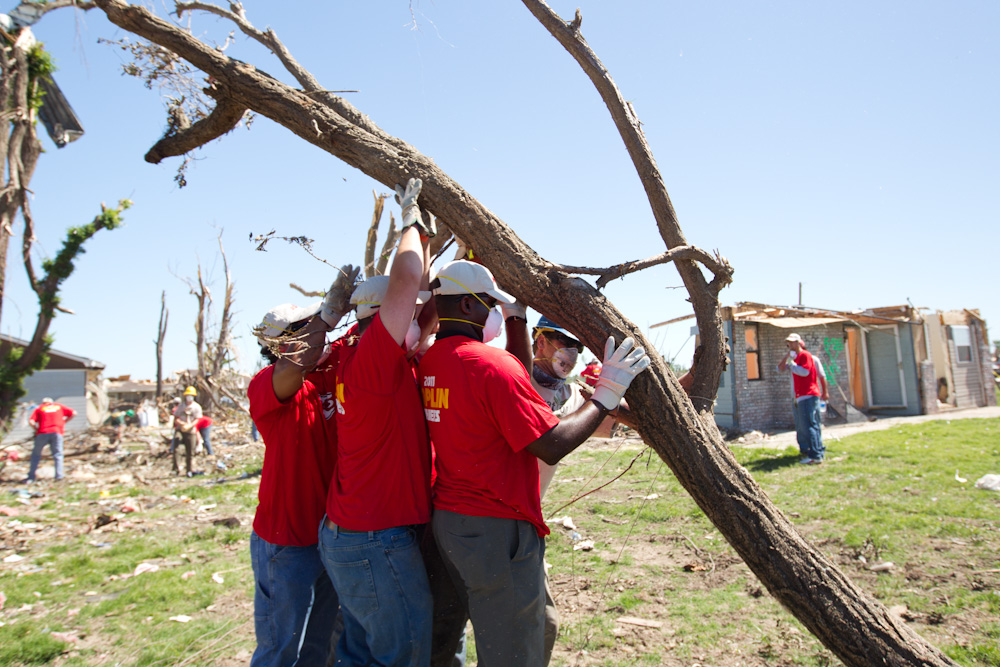 Mark Wilson, an AmeriCorps member with the Iowa Conservation Corps, assists Kansas City Chiefs players with the removal of tree debris in Joplin, MO. (Photo by Scott Julian, 2011)