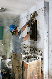 An AmeriCorps member guts a damaged home in St. Bernard Parish, LA, on the first anniversary of the Hurricane Katrina recovery in 2006. (Corporation for National and Community Service photo)