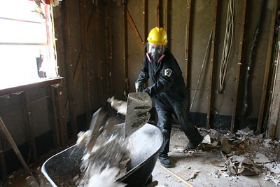An AmeriCorps NCCC member shovels drywall into a wheelbarrow during a cleanup in St. Bernard Parish, LA, on the first anniversary of the Hurricane Katrina recovery in 2006. (Corporation for National and Community Service photo)