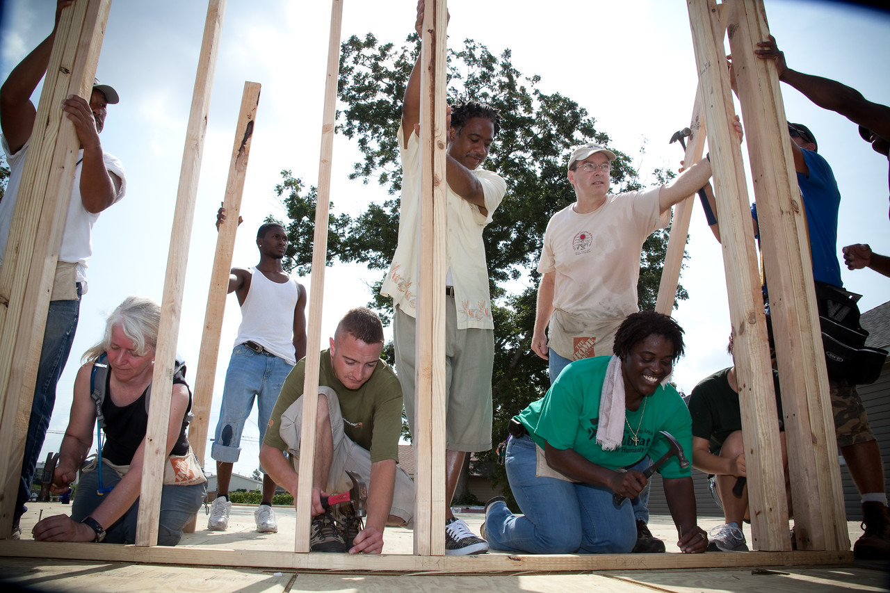 Together, volunteers erect the structure of a new home built by Habitat for Humanity in post Hurricane Katrina New Orleans.