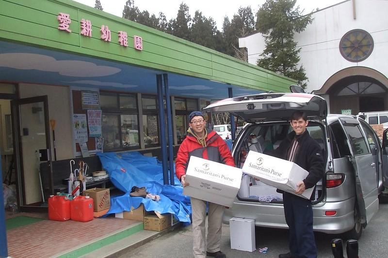 Eric Takamoto & Kent Muhling unloading boxes in disaster zone