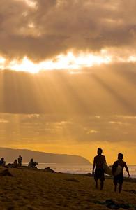 Surfers walking along the beach at sunset  North Shore of O'ahu, Hawai'i