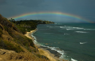 Rainbow from Diamond Head Bluff   Surfers paddling out to surf  O'ahu, Hawai'i