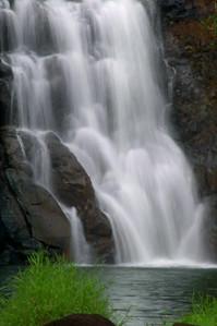 Close-up of Waimea Falls  The 40-foot Waimea Falls cascades down the rocks into the Kamananui Stream that flows through Waimea Valley, into the adjacent white sandy beach of Waimea Bay and into the ocean.  North Shore of O'ahu, Hawai'i