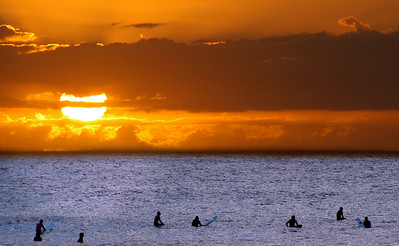 Silhouettes of surfers waiting for one last chance to catch a wave at sunset  North Shore of O'ahu, Hawai'i