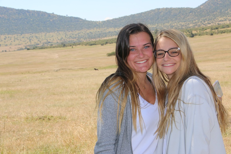 . Emily Chmela, left, and Emma Scopa, right, both 17-year-old Tewksbury Memorial High School seniors, brought school supplies to the Embiti Primary School in Kenya during a family trip. Now, they are raising funds for a new school building there. COURTESY PHOTO
