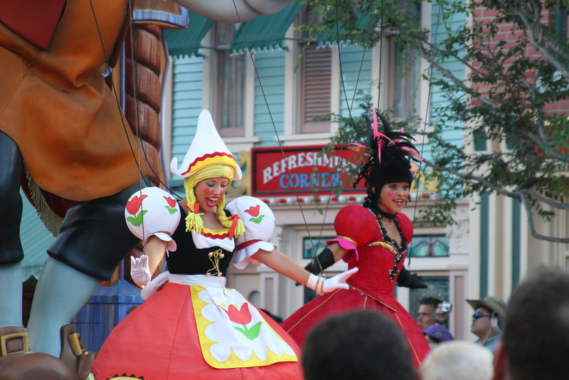 A pair of cast members in a parade down Main Street in Disneyland, CA.