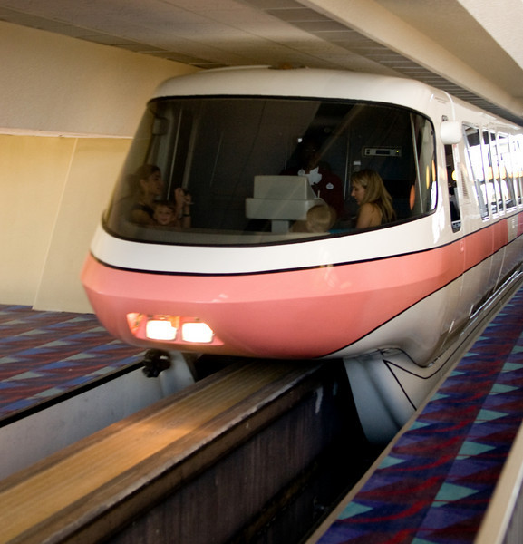 Monorail trains of Walt Disney World. This train is pulling away from the stop inside the Contemporary Hotel. Note the people riding up with the train operator. Yes, one of them is taking a picture of the other people in the nose.