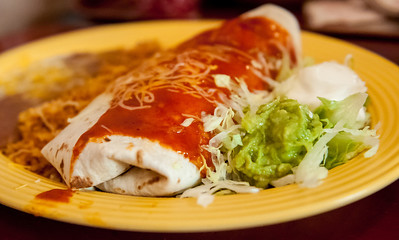 "Burrito Sonora - ""Fajita Style"" Beef, Chicken or Vegetables plus Refried Bean and Cheese. Wrapped in a Flour Tortilla and topped with a traditional Guajillo Sauce."