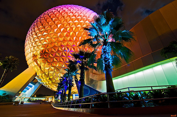 Palm trees line the path to Spaceship Earth at night.