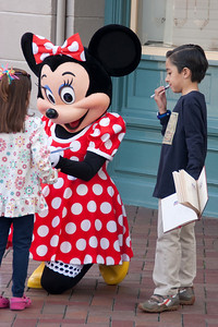 On Main Street, Minnie Mouse signs autographs.
