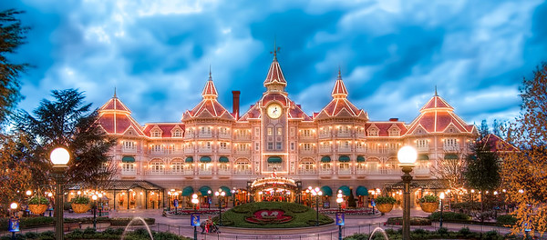 Disneyland Hôtel in the Evening - Stan  Le Disneyland Hotel est sans conteste le plus luxueux et le plus impressionnant du resort. Reconnaissable aisément à ses couleurs mauves et son architecture typique victorienne du début du 19è siècle, il plonge le visiteur au sein même de l'ambiance qu'il va découvrir sur Main Street, en passant les portes du Disneyland Park. De jour, il nous étonne déjà, mais c'est de nuit qu'il révèle toute sa splendeur, illuminé de plus de 10.000 ampoules, que les eaux de ses jardins font se balancer à la surface. Il ne s'éteindra que lorsque les premiers rayons du soleil le baigneront de leur clarté matinale.  The Disneyland Hotel is unquestionably the most luxurious and the most impressive hotel of the Resort. Easily recognizable thanks to its purple color and its typical vitorian architecture, it immerses the visitor within the atmosphere he will discover in Main Street, after he passed the Disneyland Park's gates. During the day, it amazes us but it is at night that all its splendor is revealed :enlightened by more than 10,000 bulds. It won't switch off until the first sunbeams bathe it.