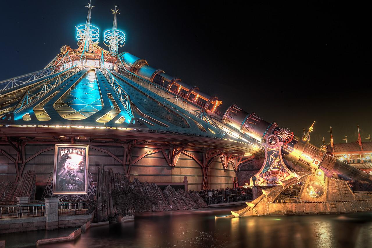 Last trip for the day - Stan<br /> <br /> Space Mountain est l'une des attractions phares que l'on retrouve dans tous les Magic Kingdom. Celui de Disneyland Paris, construit en 1995, est différent des autres sur deux points principaux :<br /> <br /> - Son système de catapulte, une première dans l'Histoire de DIsney. Il est basé sur celui utilisé à bord des porte-avions.<br /> <br /> - Sa thématisation : reprenant des couleurs et un style steampunk, les Imagineers se sont inspirés de l'univers de Jules Verne pour le décorer, et en faire de même pour tout DIscoveryland.<br /> <br /> Si de jour sa façade dorée reflète les rayons du soleil, c'est de nuit qu'il dévoile ses jeux de lumières, prêt à faire embarquer toujours plus de spationautes.<br /> <br /> <br /> Space Mountain is an attraction we can find in all the Magic Kingdoms. The Disneyland Paris one was built in 1995 and it differs from the other on two points :<br /> <br /> -its catapult system is new in the Disney's History. It is based on those used on aircraft carriers.<br /> <br /> -its thematic is inspired by the universe of Jules Verne. The Imagineers used steampunk colors and style.<br /> <br /> If during the day the golden frontage reflects sunbeams, it's by night the games of light are revealed.