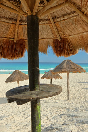 Thatch shade umbrellas with drink shelf at Playa Delfines, Cancun, Quintana Roo, Mexico. © 2018 Kenneth R. Sheide