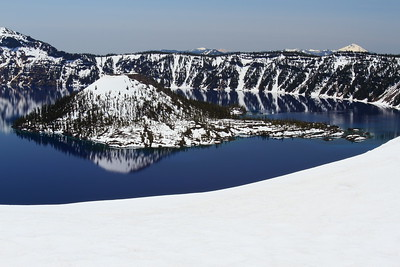 View of Wizard Island from snow-covered edge of Crater Lake, OR with Mt McLoughlin and Mt Shasta visible in distance.  © 2014 Kenneth R. Sheide