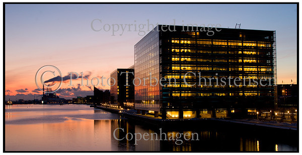 Kontorbygninger i aftenlys med rød solnedgang og blå himmel fotograferet fra Langebro. Foto: Torben Christensen  København ©