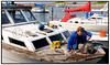 Martin, der bor sammen med kæresten i deres husbåd Mille 2 i Københavns Fiskerihavn, benytter sig af det fine forårsvejr til at komme i gang med en hårdt tiltrængt istandsættelse af båden. . Foto: Torben Christensen  København © Ayoe,  Sanni