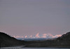 Ferga mellom Bognes og Lødingen like før den går bak Barøya på tur mot Lødingen. Foto fra Efjord. I bakgrunnen fjellene i Vesterålen. Mørketidsbilde med rødt lys på morgenhimmelen (kl 10 1. januar)