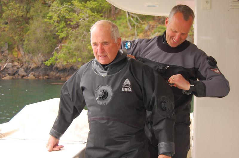 Joe zips Bill's drysuit