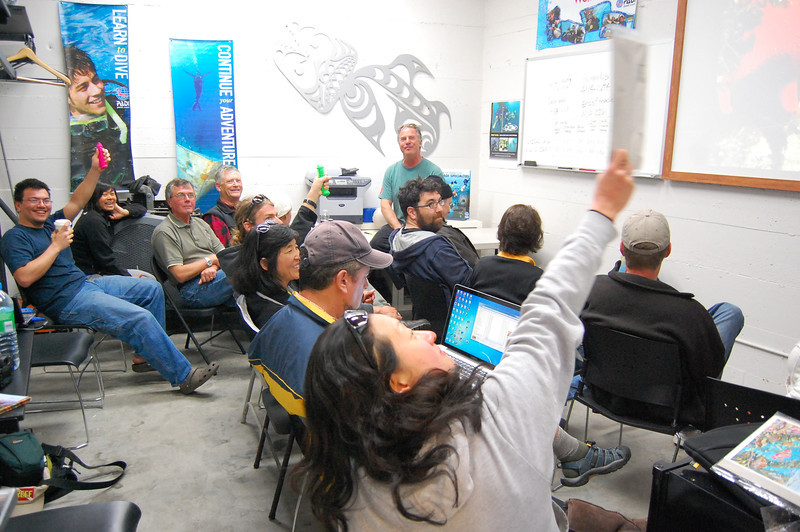 """Maria Kyong (foreground) and the rest of the group at our daily debriefing session at Seven Seas Scuba. Showing off John Wolfe's fluorescent """"sea cucumbers""""."""