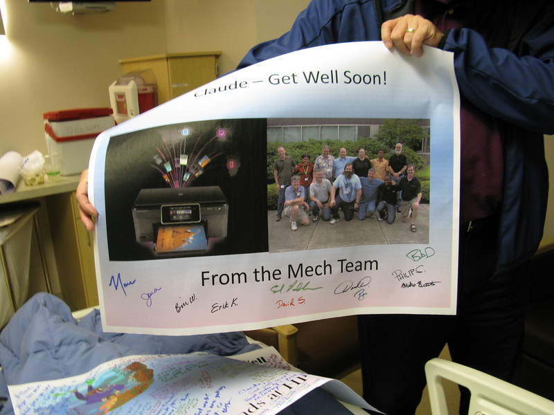 The mech team signs a large poster of get-well wishes