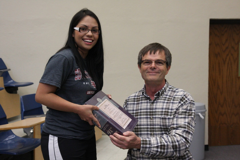 Elizabeth Valle receives a CRC Handbook from Dr. Cox for the Outstanding Freshman Chemistry Award.