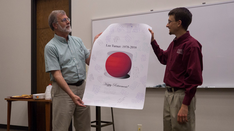 Dr. Nick Zoller presenting a poster signed by students and faculty to Dr. Turner for his retirement!