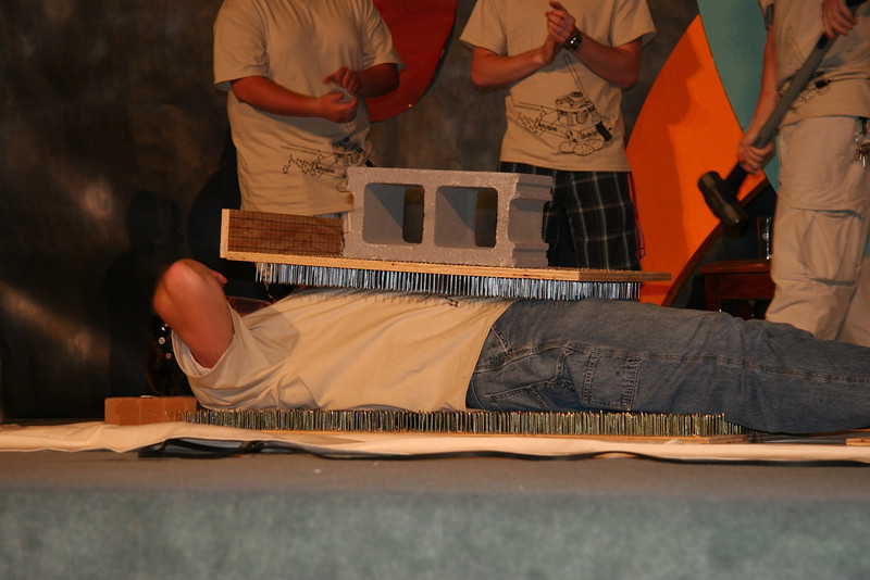 "Further displaying the AMAZING properties of pressure, Dr. Winslow demonstrates the bed of nails with the ""Winslow Sandwich"": a bed of nails, Dr. Winslow, another bed of nails, a concrete block, and Dr. Cox's sledgehammer."