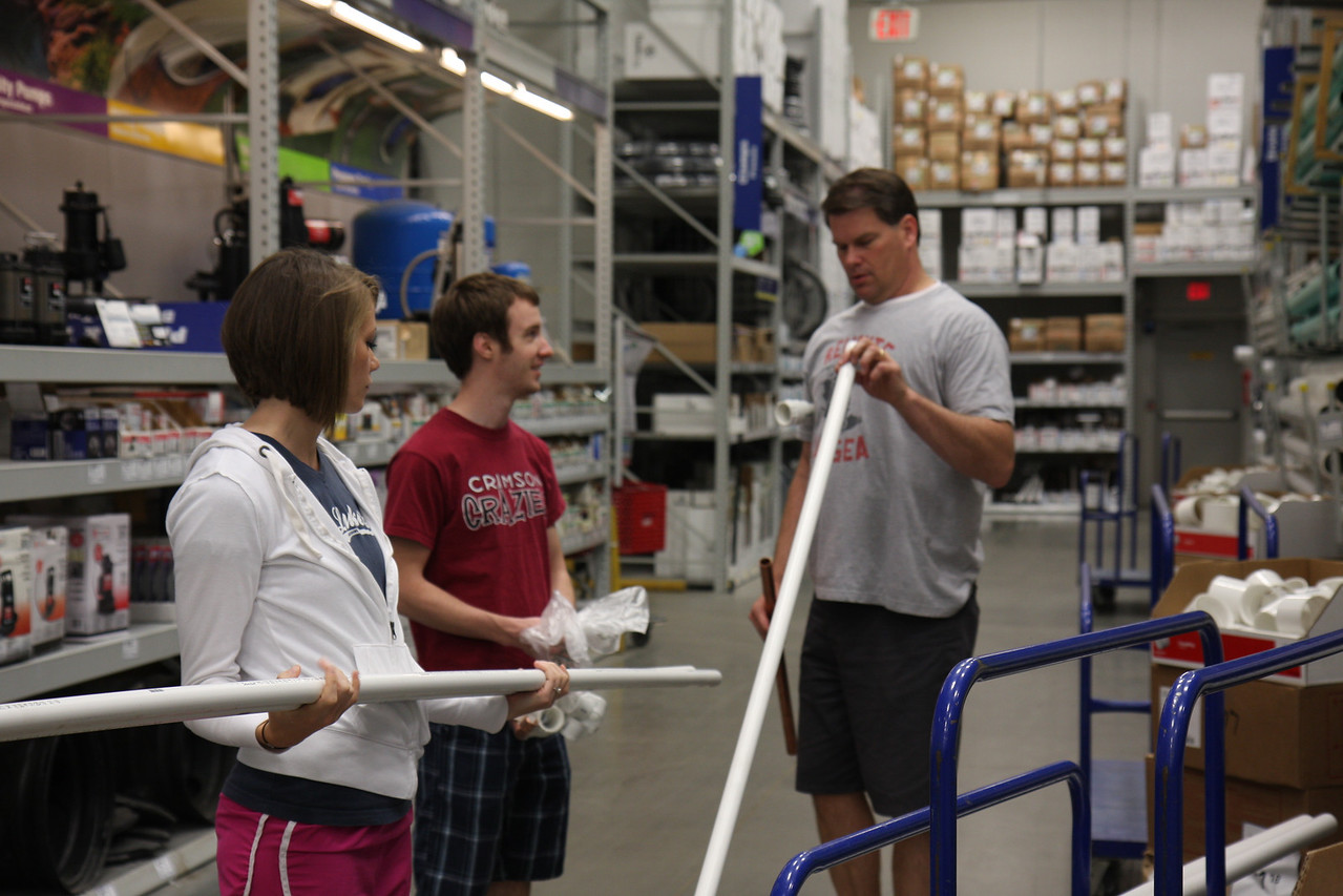 Choosing the perfect PVC piping for the potato gun, Dr. Winslow instructs the students on why they need a specific size of pipe. The team came to Lowe's to get longer pipes to maximize the time the explosive pressure acts on the projectile.