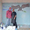 An artist poses with the owner of 911 Beauty Salon as they come together on 12/6/14 to beautify the town by painting the boards that stores put up for security to protect against riots and looting after the grand Jury decided not to indite Officer Wilson for the killing of Michael Brown.