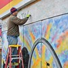 Residents from Ferguson and surrounding areas come together on 12/6/14 to beautify the town by painting the boards on an AutoTire  stores put up for security to protect against riots and looting after the grand Jury decided not to indite Officer Wilson for the killing of Michael Brown.