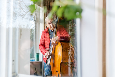 """Sergio Biseo, in his eighties, plays his double bass. He and his wife were sad not to see his grandchildren this year, but they kept busy with various video calling over Christmas.<br /> ©KT Watson 