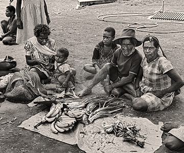 3 generations selling their garden goods at a market in Papua New Guinea.  Bananas, onions, peas and more.