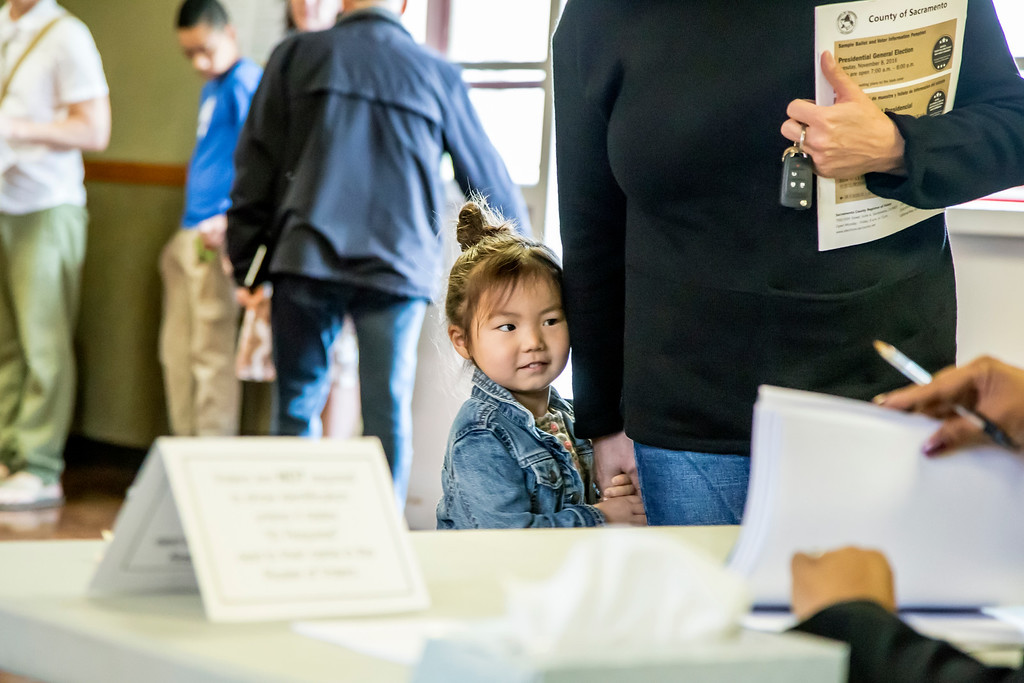 """Four-year-old Elliott Webb hides behind her mother, Toni Webb, who checks in to obtain her ballot. Photos and story on """"A Day in the Life of a Neighborhood Precinct"""" for Comstock's online. <br /> <a href=""""http://www.comstocksmag.com/photo-gallery/day-life-neighborhood-precinct"""">http://www.comstocksmag.com/photo-gallery/day-life-neighborhood-precinct</a>"""