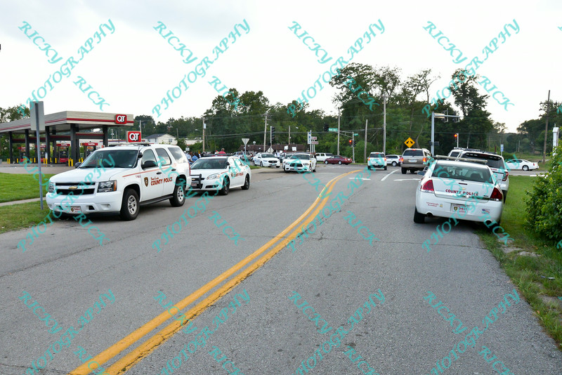 """Police cars lined up at the site where protesters gathered during the second day of protests in Ferguson Missouri on West Florissant in front of the QT that was burned to ruins the night before during the riot.  Protesters are upset over the shooting of """"unarmed"""" Michael Brown an 18 year old black male by a member of the Ferguson Police Department."""