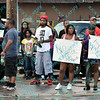 """Protesters hold up signs calling for justice during the second day of protests in Ferguson Missouri on West Florissant in front of the QT that was burned to ruins the night before during the riot.  Protesters are upset over the shooting of """"unarmed"""" Michael Brown an 18 year old black male by a member of the Ferguson Police Department."""