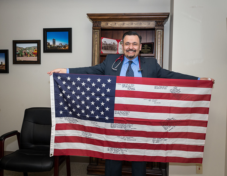 Dr. Mohammed Bahaa Aldeen holding an American flag signed by the team he served with as a cultural advisor for USMC Civil Affairs Team CA2 2/11 during the Iraq war. [Shaie Williams for Amarillo Globe News]