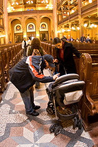 The tour guide playing with a little baby - Moran is walking down the aisle...