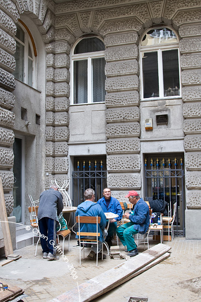 Workers on a break in a small courtyard.