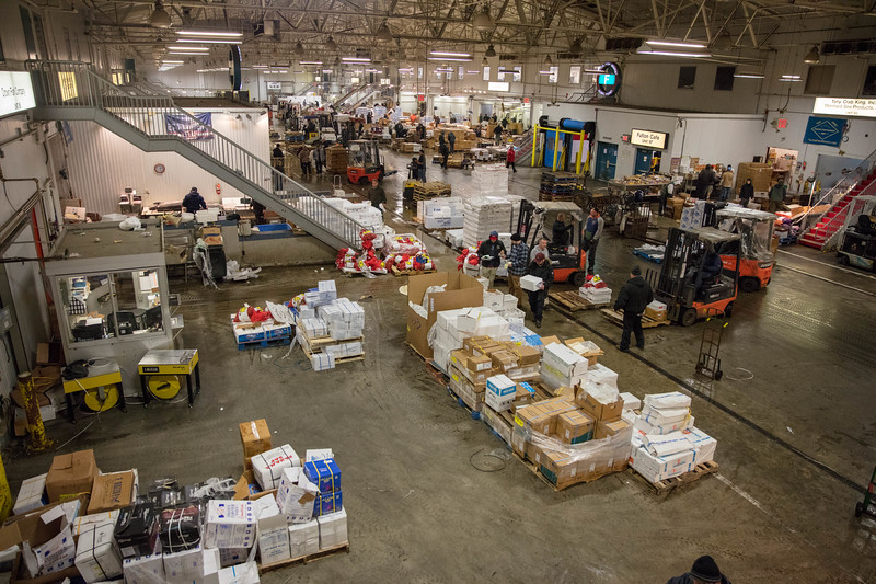 Seafood samples are displayed in front of pallets stacked with boxes, forklifts constantly whirring between the front lines and back storage areas