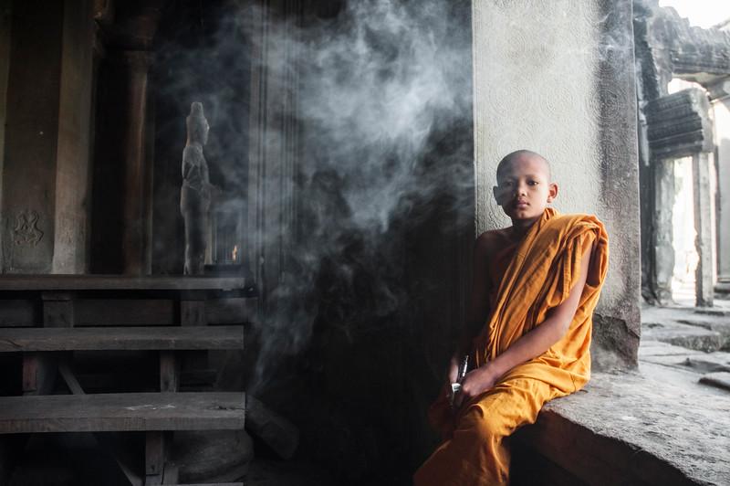 Cambodian child monk smoking at Angkor Wat