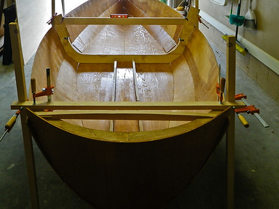 One central rib was used to bend the plywood around so the shape of the boat would be symmetrical.  The stern section was added with some difficulty but finally fit. Now it was starting to look like a boat. Held together with a prayer and MANY copper stitches. We next leveled and squared up the stern and sides.