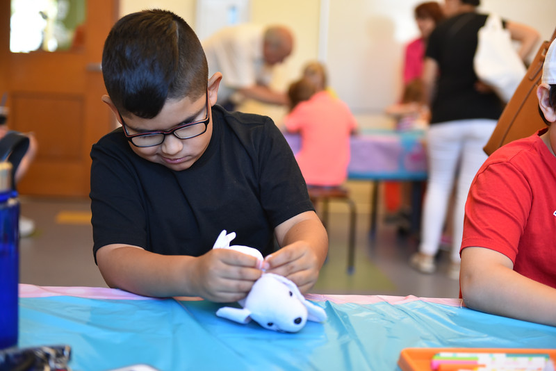 Jovani Calderon, 7 of Leominster decorates a stuffed dog during the Dog Days Craft Time held at the Leominster Public Library on Monday.  SENTINEL & ENTERPRISE JEFF PORTER