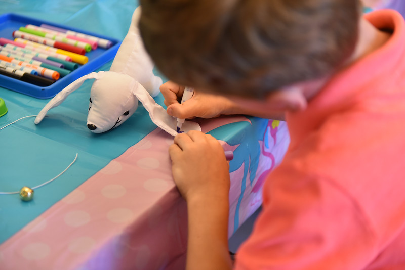 Kids are given stuffed dogs to draw decorations on during Dog Days Craft Time held at the Leominster Public Library on Monday.  SENTINEL & ENTERPRISE JEFF PORTER