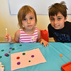 Alexandra Woodland, 4 (left) and brother Seth Woodland, 9, of Leominster partner up to create decorations for the Dog Days Craft Time held at the Leominster Public Library on Monday.  SENTINEL & ENTERPRISE JEFF PORTER