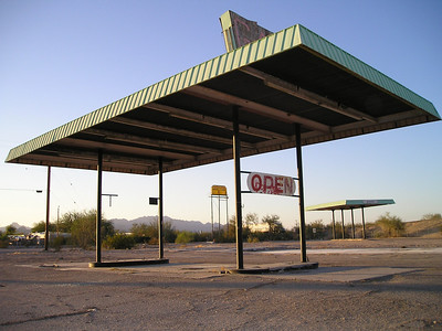 We've just crossed a hundred miles of desert nothingness after Palm Springs and are nearing the oasis of Blythe, when there's a loud flflflflflflflf WHAP under the car. I hold tight to the steering wheel but the car keeps moving smoothly and there's no feeling of tire damage. But we've just spent the last 15 minutes talking about flat tire experiences, so we think that maybe we should pull over and check the tires. We do so, at this convenient ghost service station, which interestingly remains open.