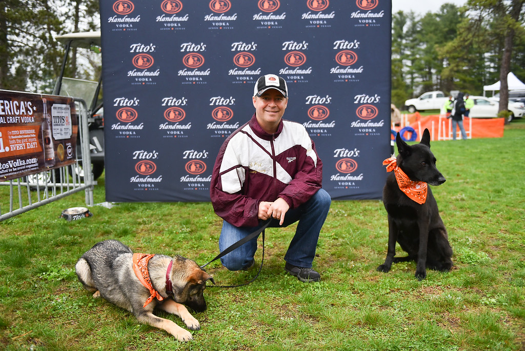 . (04/29/18 DEVENS) Timothy Burke of Tito\'s Handmade Vodka poses for a photo with dogs Luna (left) and Logan (right) during Sunday\'s Dogs2Vets Festival on Fort Devens.  SENTINEL & ENTERPRISE JEFF PORTER