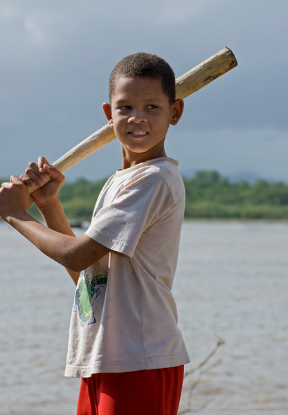 Boy with handmade baseball bat, Rio San Juan, Dominican Republic.